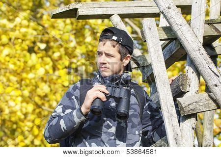 Boy with binoculars on wooden stairs