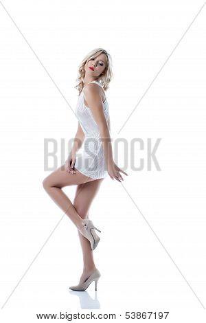 Flirtatious slim girl posing in white short dress