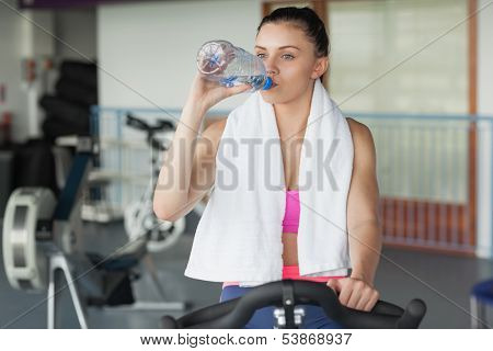 Tired young woman drinking water while working out at exercise bike in gym