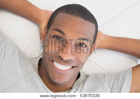 Close up portrait of a smiling young Afro man resting in bed at home