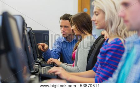 Side view of teacher showing something on screen to student in the computer room