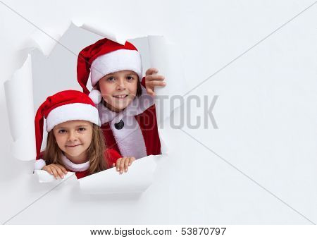 Happy kids in santa outfits looking through hole in paper - christmas joy concept, with copy space