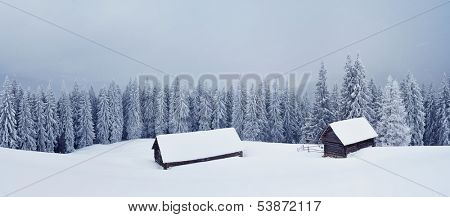 Landscape panorama of a mountain valley in the winter. Hut and barn in the mountains. Ukraine, Carpathian, the ridge Kukul