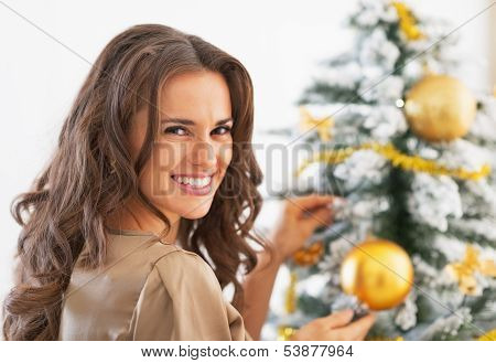 Portrait Of Happy Young Woman Decorating Christmas Tree With Chr