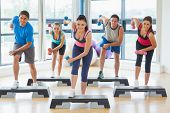 stock photo of step aerobics  - Full length of instructor with fitness class performing step aerobics exercise with dumbbells in a gym - JPG