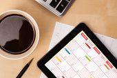 image of wooden table  - Workplace with tablet pc showing calendar and a cup of coffee on a wooden work table close - JPG