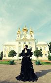 foto of evil queen  - Beautiful woman in black dress posing next to the palace - JPG