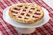 pic of cherry pie  - Cherry pie with lattice top on fall themed napkin and mini pumpkins - JPG