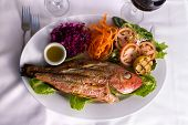 picture of plate fish food  - Full cooked tilapia fish served in a plate with vegetables and fish sauce complimented with red vine - JPG