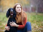 girl and her dog gordon setter in the autumn park