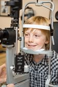 picture of slit  - Smiling boy undergoing eye examination test with slit lamp in store - JPG