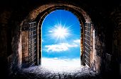 stock photo of tunnel  - Dark tunnel corridor with arch opening to the sun - JPG