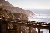 stock photo of pch  - A view of Bixby Bridge out to the Pacific Ocean near Big Sur California USA - JPG