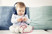 stock photo of cute innocent  - Cute baby boy sitting on sofa and listening music at headphones while  looking at iphone - JPG