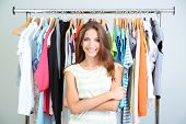 stock photo of department store  - Beautiful young woman near rack with hangers - JPG