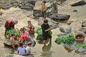 Asian With Children, Washed Greens In A Rural River.