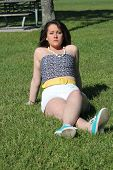 image of halter-top  - Pretty teen in white shorts and halter top sitting on the grass in a small park - JPG