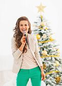 picture of christmas song  - Happy young woman singing in front of christmas tree - JPG