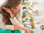 image of sad christmas  - Stressed young woman in front of christmas tree - JPG