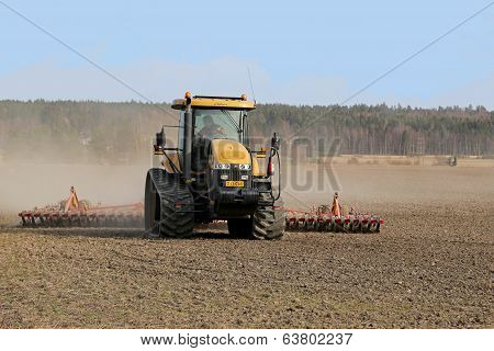 Caterpillar Challenger Crawler Tractor And Potila Seedbed Cultivator On Spring Field