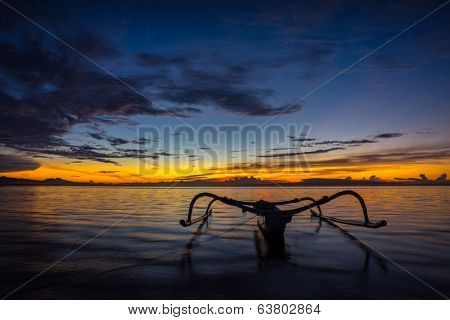 Fisherman out-rigger boat on the shallow water on Bali beach at sunrise