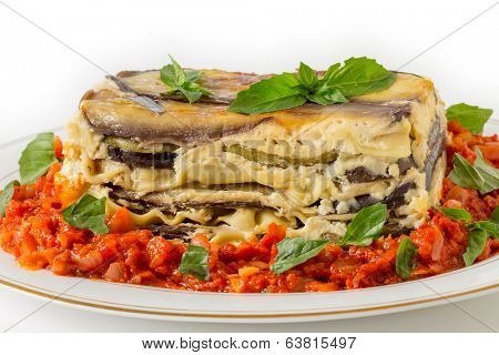Vegetable lasagne, made with courgettes and eggplants (zucchini and aubergines), pasta sheets and bechamel sauce, served with a tomato and onion sauce and a basil garnish, side view