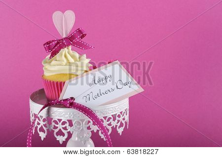 Happy Mothers Day Pink Heart Cupcake On White Cupcake Stand With Greeting Gift Tag Against A Feminin