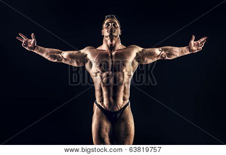 Handsome muscular bodybuilder posing over black background. Glory of the champion.
