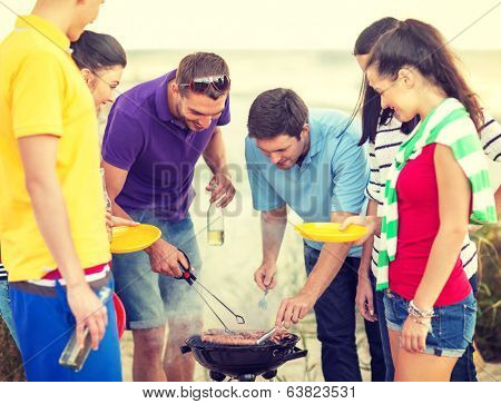 summer, holidays, vacation, happy people concept - group of friends having picnic and making barbecue on the beach