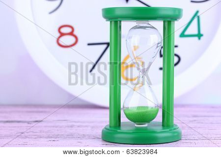 Hourglass and big clock on light background
