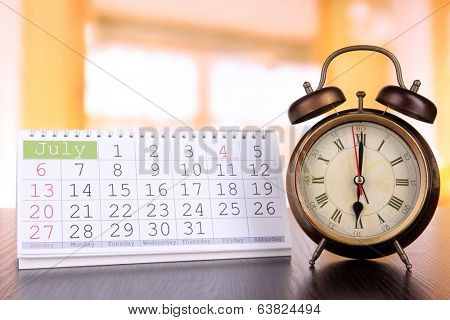 Alarm clock  and calendar on bright background