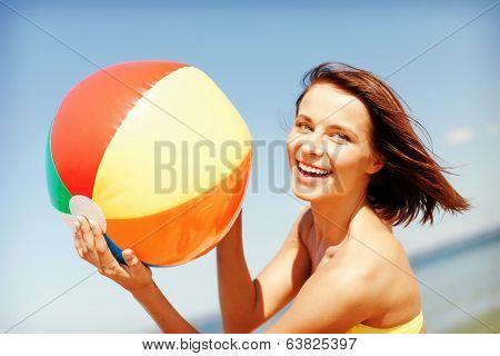 summer holidays, vacation and beach activities concept - girl in bikini playing ball on the beach