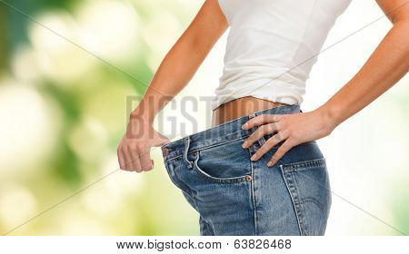 healthcare, diet and fitness concept - close up of female showing big jeans