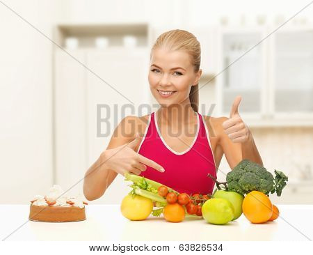 fitness, healthcare and diet concept - smiling woman with fruits and cake pointing at healthy food