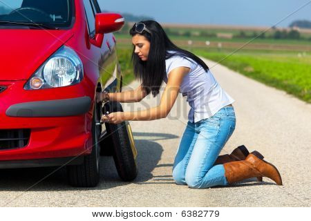 Young Woman Changing Tire