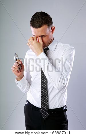 Portrait of a businessman holding glasses and rubbing his eyes on gray background