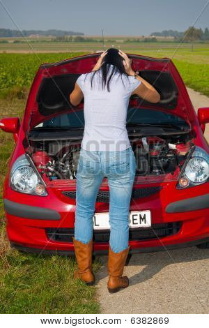 Stressed Woman Looking At Car Engine