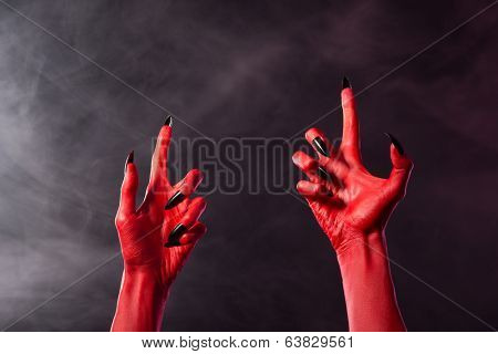 Creepy red devil hands with black sharp nails, Halloween theme