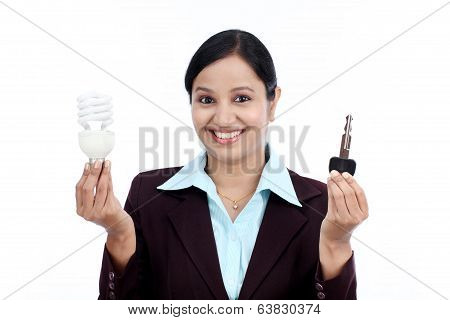 Happy Young Business Woman Holding Bulb And Key