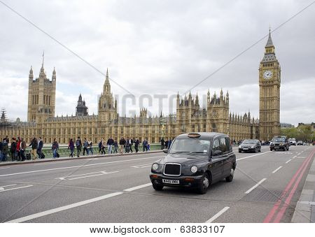 LONDON, UK - APRIL 18, 2014: Black taxi cab in front of the Palace of Westminster.