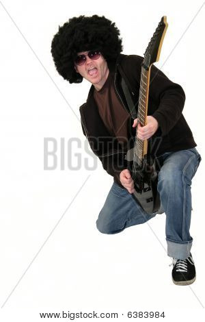 guitarist with a wig playing an electrical guitar while kneeling down