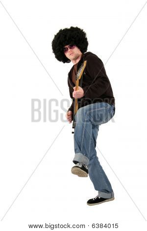 young guitarist with a wig and sunglasses playing a guitar standing on one leg