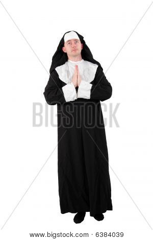 young male actor in a nun´s costume with praying hands