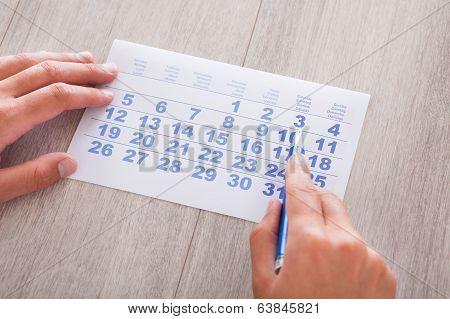 Hand Holding Calendar And Pen