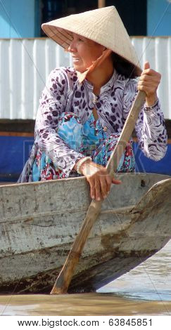 Vietnamese woman in conical hat paddling boat in Mekong Delta