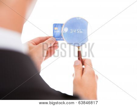 Man Holding Credit Card And Magnifying Glass