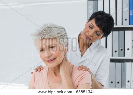 Female chiropractor looking at senior woman with neck pain in the medical office