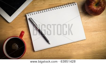 Overhead of notepad and pen on a cluttered desk