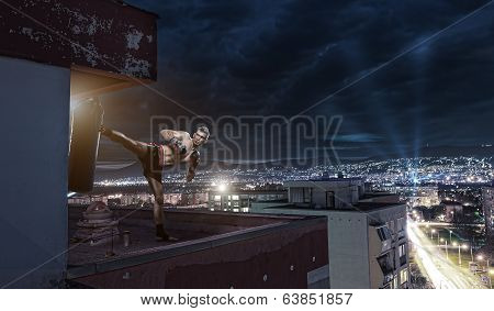 Young man boxing training on top of the house above the city