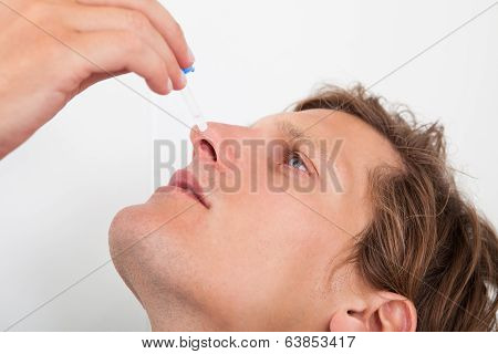 Young Man Using Nasal Spray